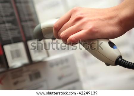 Store. Barcode reader in the hand of the girl. Shallow DOF. - stock photo