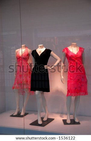 Store window with dressed mannequins in shopping mall - stock photo