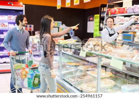 Storekeeper serving two customers - stock photo