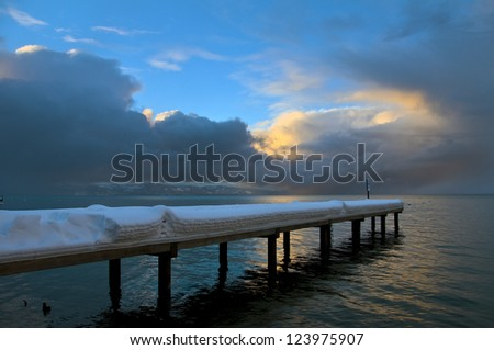 storm approaching a snow covered pier - stock photo