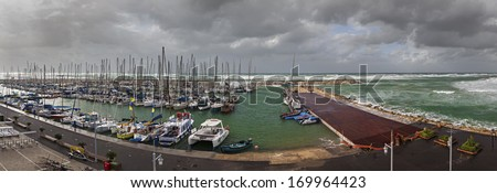 Storm by the Mediterranean sea and yachts in a marina - stock photo