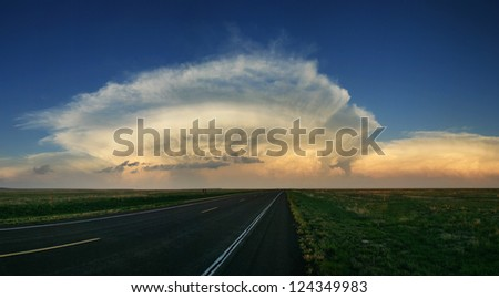 storm cell anvil head clouds above the great plains horizon just before sunset - stock photo