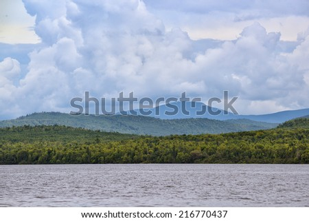 Storm clouds brewing over the mountains above Moosehead lake - stock photo