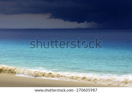 Storm clouds coming towards tropical ocean white sand beach - stock photo