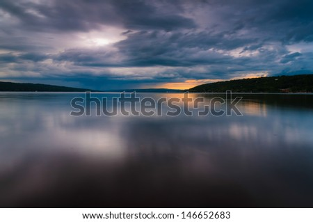 Storm clouds move over Lake Cayuga in a long exposure, seen from Stewart in Ithaca, New York. - stock photo