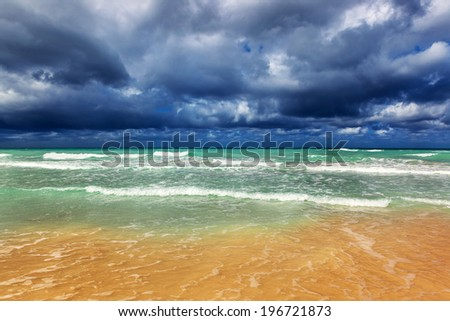 Storm clouds over a sandy beach - stock photo