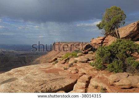 Storm clouds over red rocks in Canyonlands National Park - stock photo