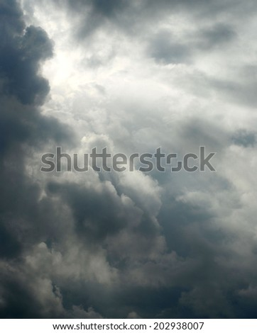 Storm clouds with sun trying to come through. Vertical image has sun positioned in upper left corner. Sun's rays are coming from behind thunderstorm clouds. Could be concept of hope or of doom - stock photo