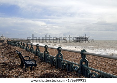 Storm damage on Brighton seafront on the south coast of England, with beach shingle washed up on to Promenade and Palace Pier in the background. - stock photo
