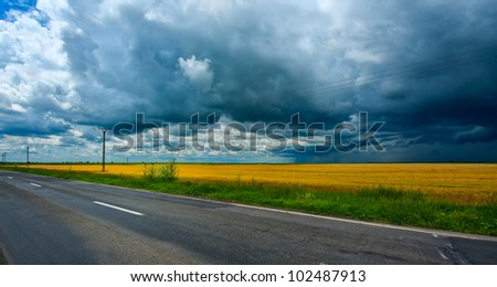 Storm dark clouds over field and empty road - stock photo