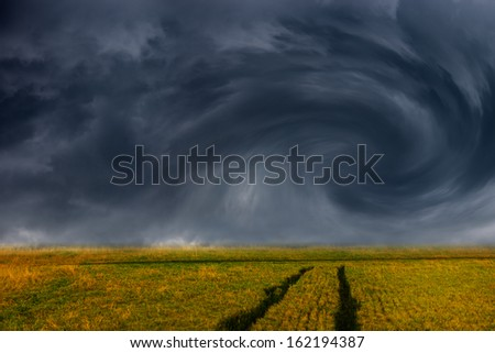 Storm dark clouds over field - dramatic sky. - stock photo