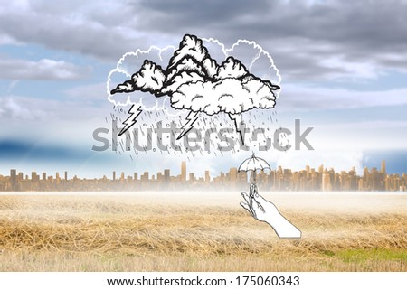Storm doodle with hand holding tiny umbrella against large city on the horizon - stock photo