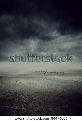 storm landscape with dry cracked land - stock photo