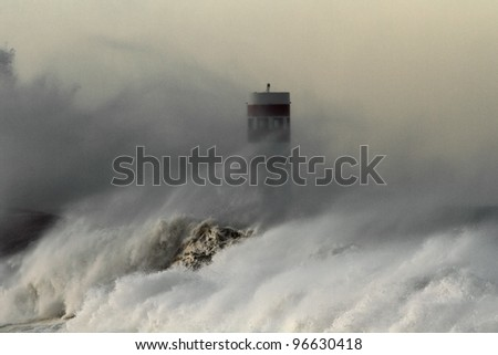 Storm waves over beacon at the mouth of the Douro River in Porto, Portugal - focus on water - stock photo
