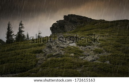 storm with rain and dark clouds on the sky on a mountain - stock photo