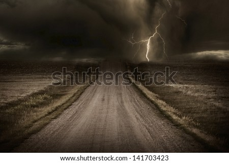 Stormy Back Country Road. Heavy Storm and Lightning Bolt in a Distans. Severe Weather Imagery Collection. - stock photo