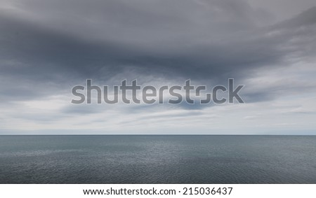 Stormy clouds over dark sea - stock photo