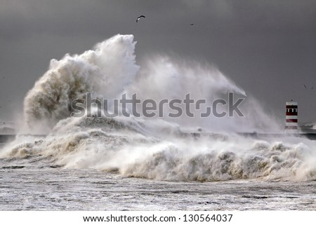 Stormy morning at the harbor of the mouth of the river Douro, in Porto, Portugal, with big waves against pier and beacon - stock photo