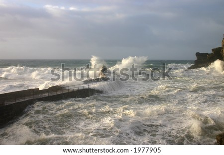 Stormy sea and waves breaking on the quay, Portreath, Cornwall - stock photo