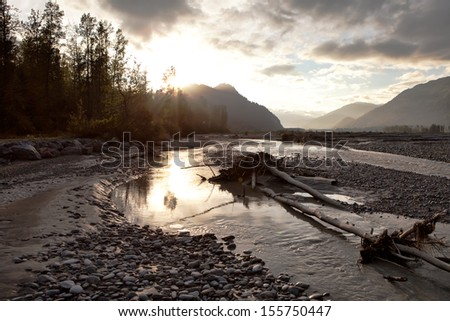 Stormy skies at sunset on the Chilkat river near Haines, Alaska. - stock photo