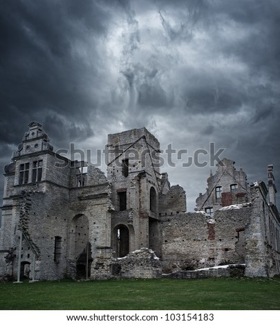 Stormy sky over ruins of manor house - stock photo