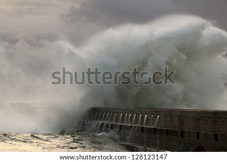Stormy sunset at the harbor of the mouth of the river Douro, in Porto, Portugal, with big waves against pier and beacon; close-up - stock photo