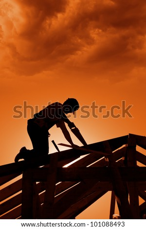 Stormy sunset on construction site with carpenter working - stock photo