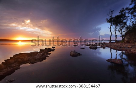 Stormy sunset over the serene waters of St Georges Basin, Sanctuary Point, Australia - stock photo