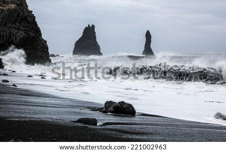 Stormy waves at black volcanic beach near famous Reynisfjara rocks at south coast of Iceland - stock photo