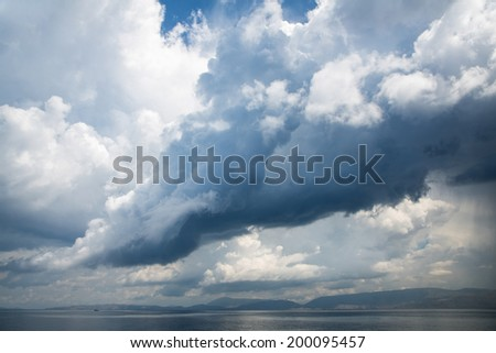 Stormy weather with big rain clouds on the sea. - stock photo