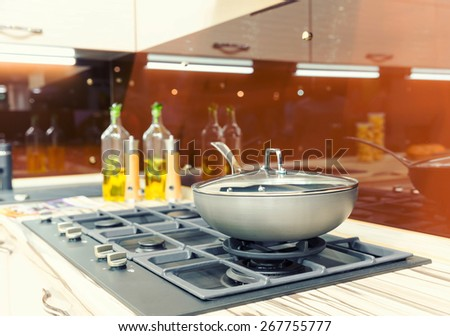 Stove with pan on the plastic modern kitchen - stock photo