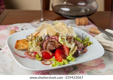 Straccetti Di Manzo Traditional Italian Warm salad with sliced fried beef, tomatoes, celery, red onion, lettuce leaf, olives decorated parmesan, olive oil and balsamic vinegar on the white plate - stock photo