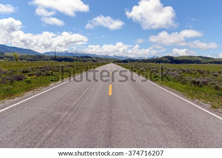 Straight and empty road running through fields,  Teton Mountains in the background. / Straight Road in Wyoming. - stock photo