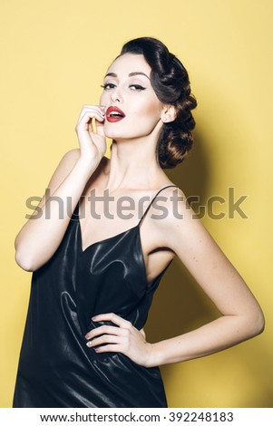Straight attractive sensual glamour retro elegant young adult woman with classic hairstyle and red lips in silk night dress indoor on yellow background, vertical picture - stock photo