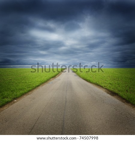 straight, empty, road, receding past green fields in countryside under dark cloudscape - stock photo