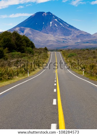 Straight highway leading to active volcano cone of Mount Ngauruhoe in Tongariro National Park, North Island of New Zealand - stock photo