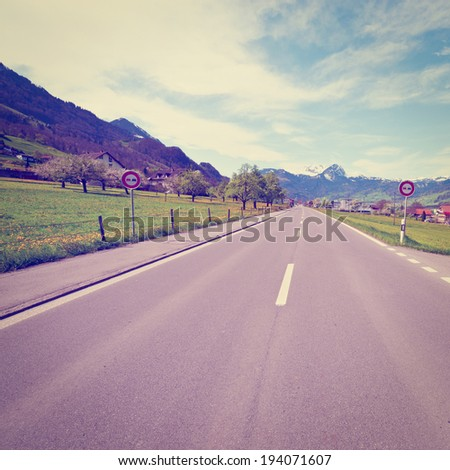 Straight Road along the Lake in the Swiss Alps, Instagram Effect - stock photo