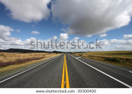 Straight road and beautiful clouds in New Zealand - North Island - stock photo