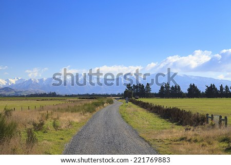 Straight rural gravel road to mountains of the Southern Alps, South Island, New Zealand. - stock photo