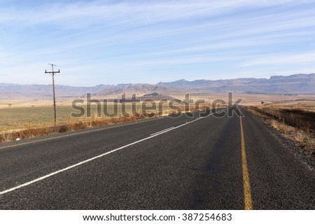 Straight rural road in dry winter landscape stretching into mountains in Drakensberg South Africa - stock photo
