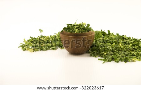 Straight view focus on shredded pandan leaf in a wooden bowl. Partially focus loose leaf behind the bowl with white background for text.  The sweet fragrance herbal tea leaf has medicinal benefits. - stock photo