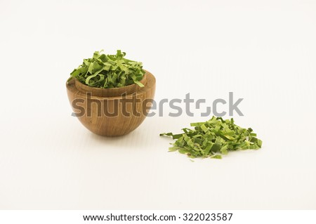 Straight view on shredded pandan leaf in a wooden bowl at left side with some outside the bowl. The leaf is use as herbal tea for its strong sweet fragrance and medicinal benefits.  White background. - stock photo