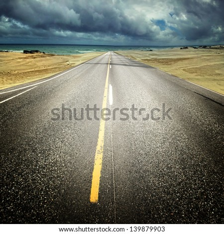straight way in nice country with dramatic clouds - stock photo