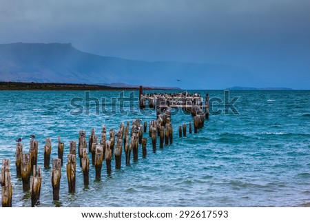 Strait of Magellan summer February afternoon. Waterfront, Punta Arenas.  Piles of the destroyed mooring act from water - stock photo