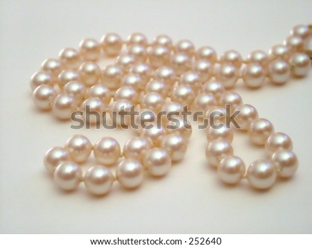 Strand of pearls against white background - stock photo