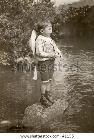 Stranded Cry-Baby - a young boy is stranded on a rock in the middle of a stream, and has a pitiful bawl-baby expression on his face.  A circa 1900, vintage photograph. - stock photo