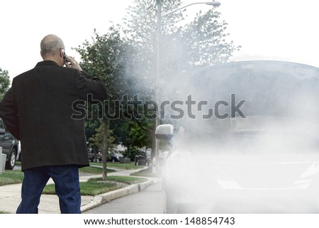 Stranded motorist driver on side of road calling on cell phone for emergency assistance help near broken down car with smoke or steam from hose leak smoking out of open automobile engine compartment - stock photo