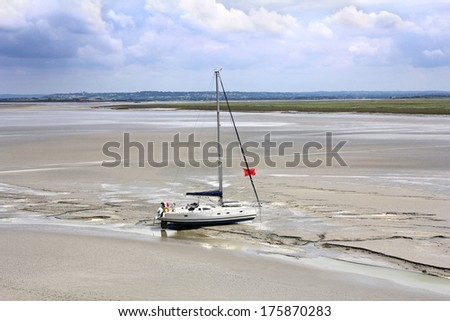 Stranded yacht near the abbey Mont Saint Michel waits tide, to set sail. Normandy, France - stock photo