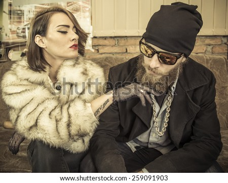 Strange couple sitting at home together on a couch. - stock photo