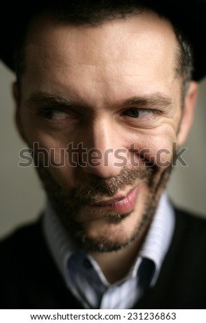 Strange funny face in great DOF of a funny man with beard and a hat - stock photo